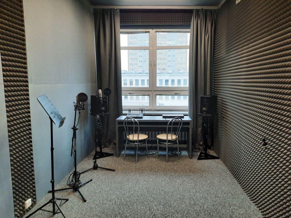 zdjęcie przedstawia studio nagrań wraz z wyposażeniem: mikrofony, głośniki