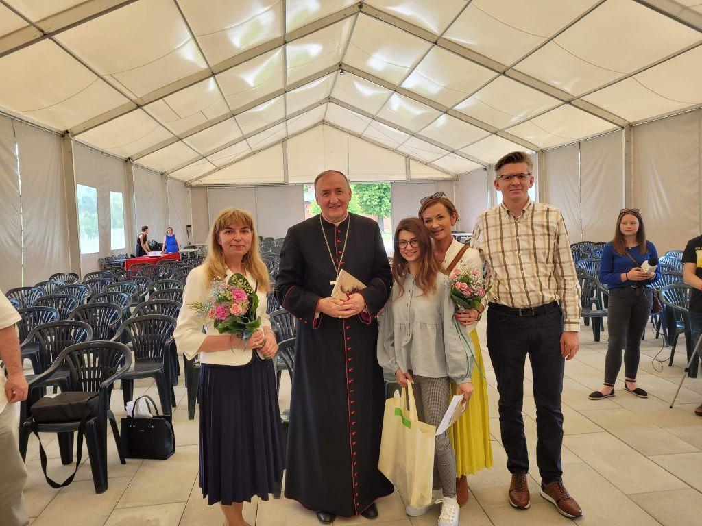 Ks.Biskup Andrzej Jeż wraz z p.katechetką Jolantą Witek i laureatkąkonkursu Oliwią Dąbrowską oraz jej rodzicami Marzeną i Waldemarem Dąbrowskimi