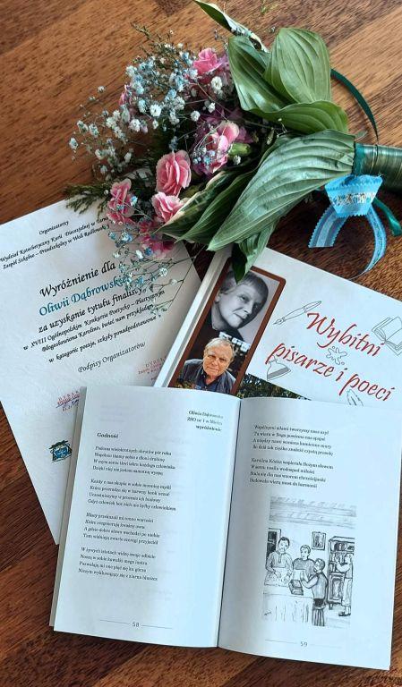 kwiaty,dyplom, książka z wydrukowanym wierszem O.Dąbrowskiej